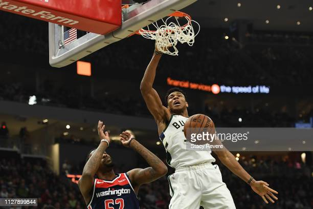 Giannis Antetokounmpo of the Milwaukee Bucks dunks in front of Jordan McRae of the Washington Wizards during the first half of a game at Fiserv Forum...