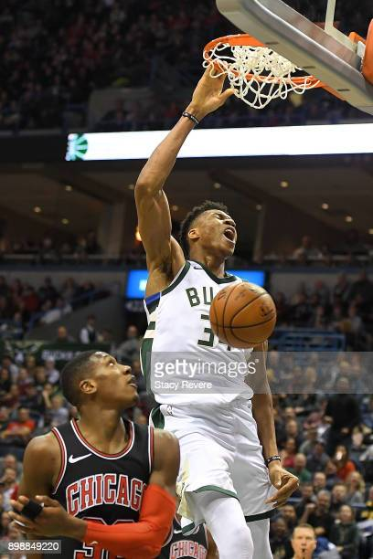 Giannis Antetokounmpo of the Milwaukee Bucks dunks in front of Kris Dunn of the Chicago Bulls during the first half of a game at the Bradley Center...