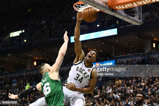 Giannis Antetokounmpo of the Milwaukee Bucks dunks over Aron Baynes of the Boston Celtics during the second half of game three of round one of the...