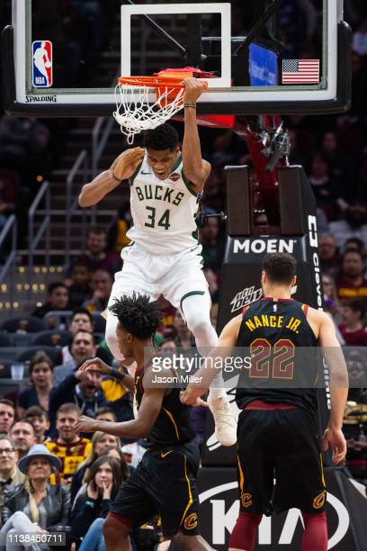 Giannis Antetokounmpo of the Milwaukee Bucks dunks over Collin Sexton and Larry Nance Jr #22 of the Cleveland Cavaliers during the first half at...