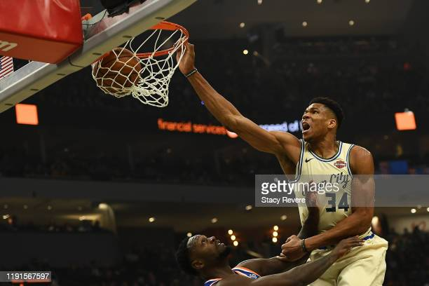 Giannis Antetokounmpo of the Milwaukee Bucks dunks over Julius Randle of the New York Knicks during the first half at Fiserv Forum on December 02,...