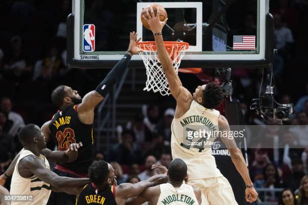 Giannis Antetokounmpo of the Milwaukee Bucks dunks over LeBron James of the Cleveland Cavaliers during the second half at Quicken Loans Arena on...