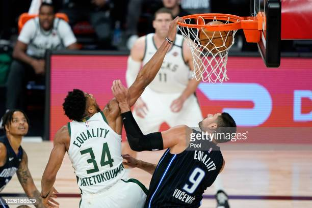Giannis Antetokounmpo of the Milwaukee Bucks dunks the ball over Nikola Vucevic of the Orlando Magic during the second half of an NBA basketball...