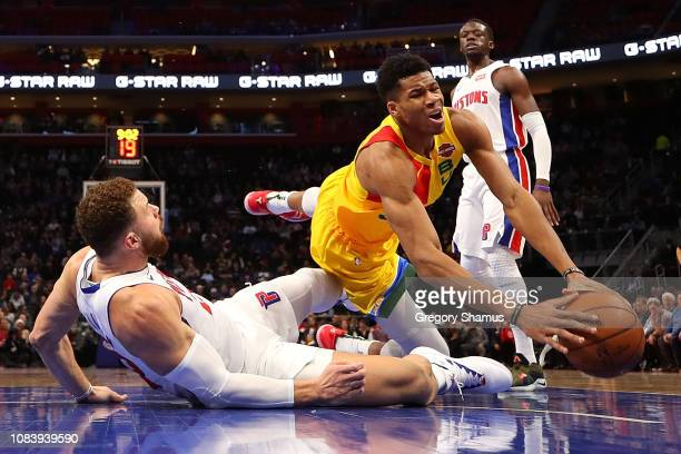 Giannis Antetokounmpo of the Milwaukee Bucks falls over Blake Griffin of the Detroit Pistons on his way to the basket during the first half at Little...
