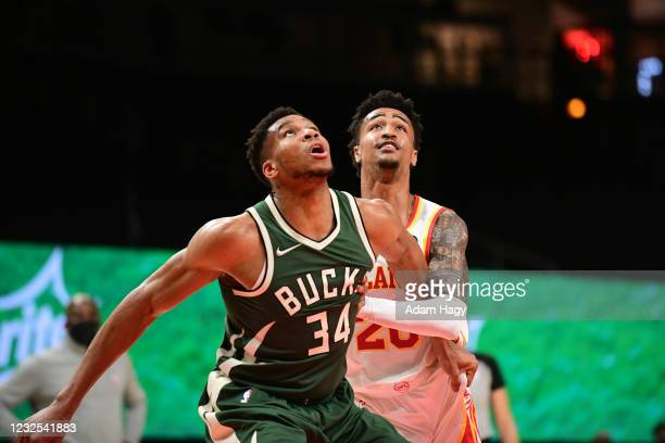 Giannis Antetokounmpo of the Milwaukee Bucks fights for position against John Collins of the Atlanta Hawks on April 25, 2021 at State Farm Arena in...