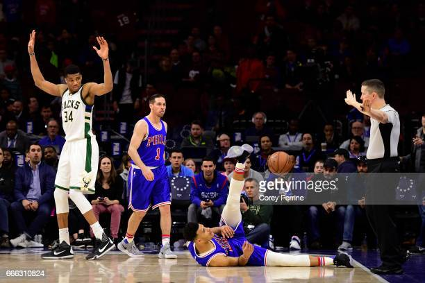 Giannis Antetokounmpo of the Milwaukee Bucks fouls Timothe LuwawuCabarrot as TJ McConnell of the Philadelphia 76ers looks on during the fourth...
