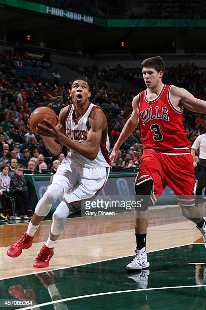 Giannis Antetokounmpo of the Milwaukee Bucks goes for the layup against Doug McDermott of the Chicago Bulls during the game on October 11 2014 at...