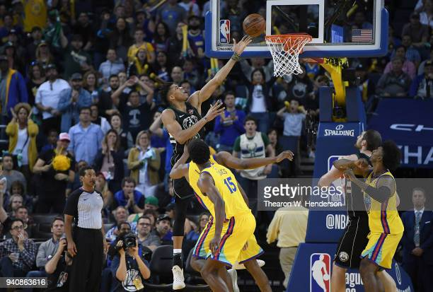 Giannis Antetokounmpo of the Milwaukee Bucks goes in for a layup over Kevon Looney of the Golden State Warriors during an NBA basketball game at...