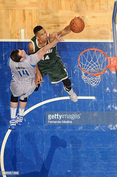Giannis Antetokounmpo of the Milwaukee Bucks goes up for a dunk against Jason Smith of the Orlando Magic on November 27 2015 at Amway Center in...