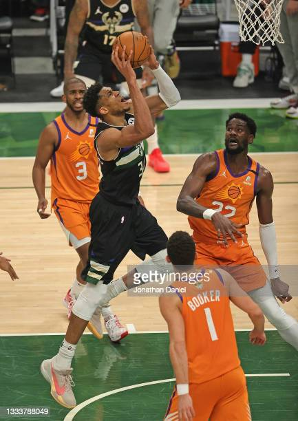 Giannis Antetokounmpo of the Milwaukee Bucks goes up for a shot over Chris Paul, Deandre Ayton and Devin Booker of the Phoenix Suns at Fiserv Forum...