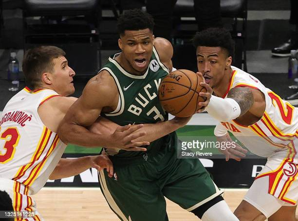 Giannis Antetokounmpo of the Milwaukee Bucks has the ball stripped by John Collins and Bogdan Bogdanovic of the Atlanta Hawks during the first...