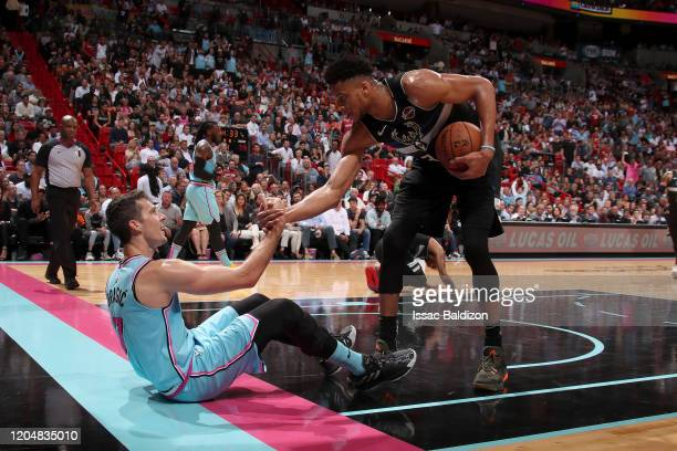 Giannis Antetokounmpo of the Milwaukee Bucks helps Goran Dragic of the Miami Heat up during the game on March 02 2020 at American Airlines Arena in...
