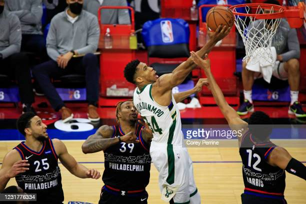Giannis Antetokounmpo of the Milwaukee Bucks hits a finger roll between Dwight Howard of the Philadelphia 76ers and Tobias Harris with Ben Simmons...