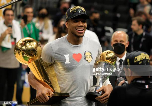 Giannis Antetokounmpo of the Milwaukee Bucks holds the Bill Russell NBA Finals MVP Award and the Larry O'Brien Championship Trophy after defeating...
