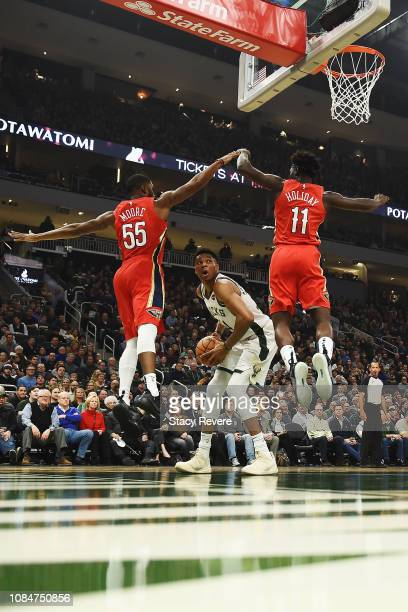 Giannis Antetokounmpo of the Milwaukee Bucks is defended by E'Twaun Moore and Jrue Holiday of the New Orleans Pelicans during the first half of a...
