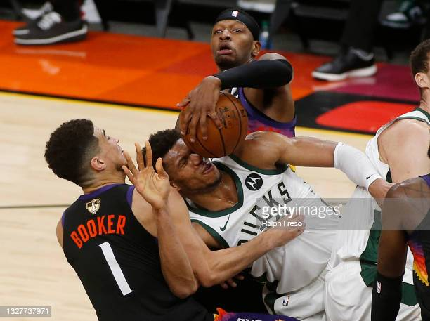 Giannis Antetokounmpo of the Milwaukee Bucks is fouled by Devin Booker and Torrey Craig of the Phoenix Suns during the second half in Game Two of the...