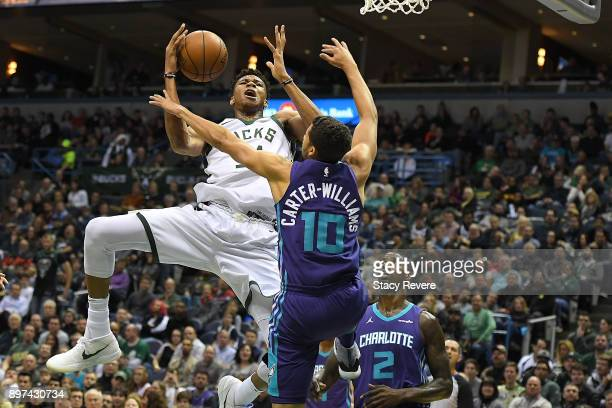 Giannis Antetokounmpo of the Milwaukee Bucks is fouled by Michael CarterWilliams of the Charlotte Hornets during the first half of a game at the...