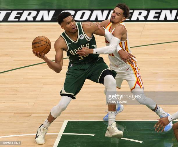 Giannis Antetokounmpo of the Milwaukee Bucks is fouled by Trae Young of the Atlanta Hawks during the second quarter in game one of the Eastern...