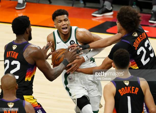 Giannis Antetokounmpo of the Milwaukee Bucks is pressured by Deandre Ayton and Cameron Johnson of the Phoenix Suns during the second half in Game One...