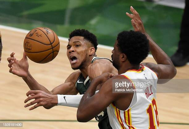 Giannis Antetokounmpo of the Milwaukee Bucks is pressured by Solomon Hill of the Atlanta Hawks during the fourth quarter in game one of the Eastern...