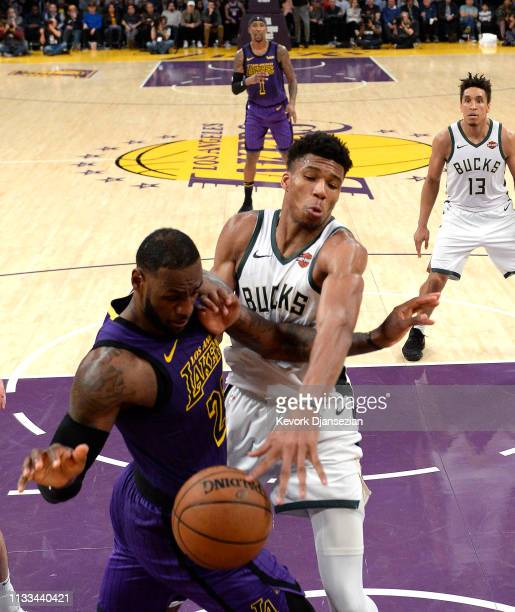 Giannis Antetokounmpo of the Milwaukee Bucks knocks the ball out of the and of LeBron James of the Los Angeles Lakers during the second half at...