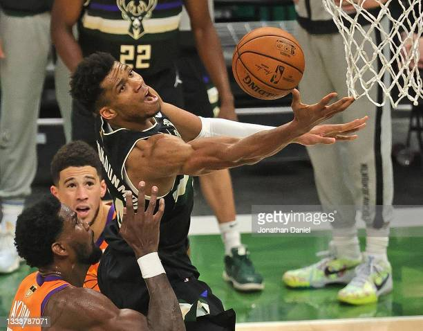 Giannis Antetokounmpo of the Milwaukee Bucks lays up a shot over Deandre Ayton nd Devin Booker of the Phoenix Suns at Fiserv Forum on July 20, 2021...