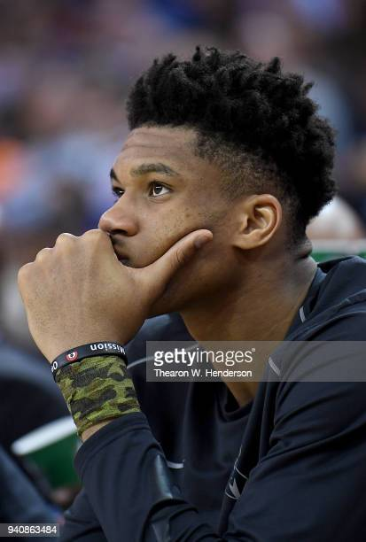 Giannis Antetokounmpo of the Milwaukee Bucks looks on from the bench against the Golden State Warriors during an NBA basketball game at ORACLE Arena...
