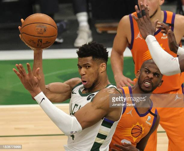 Giannis Antetokounmpo of the Milwaukee Bucks looks to pass against Chris Paul of the Phoenix Suns during the second half in Game Four of the NBA...
