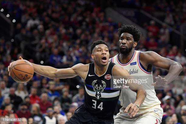 Giannis Antetokounmpo of the Milwaukee Bucks looks to pass as Joel Embiid of the Philadelphia 76ers defends during the first half of the game at...