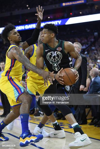 Giannis Antetokounmpo of the Milwaukee Bucks looks to pass the ball while closely guarded by Nick Young of the Golden State Warriors during an NBA...