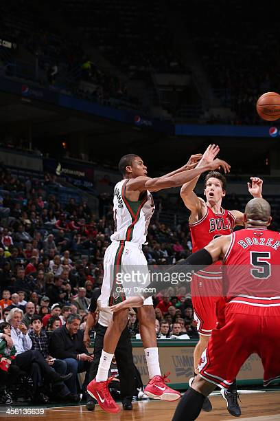 Giannis Antetokounmpo of the Milwaukee Bucks passes against Mike Dunleavy and Carlos Boozer of the Chicago Bulls on December 13 2013 at the BMO...
