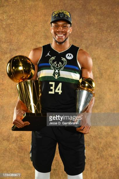 Giannis Antetokounmpo of the Milwaukee Bucks poses for a portrait with the Larry O'Brien Trophy and Bill Russell Finals MVP Award after winning Game...