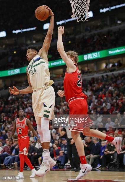 Giannis Antetokounmpo of the Milwaukee Bucks rebounds over Lauri Markkanen of the Chicago Bulls at the United Center on January 28 2018 in Chicago...