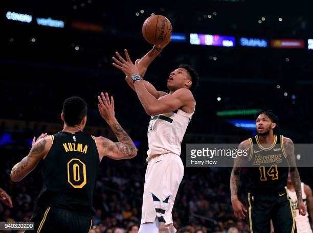 Giannis Antetokounmpo of the Milwaukee Bucks scores on a shot between Kyle Kuzma and Brandon Ingram of the Los Angeles Lakers during the first half...