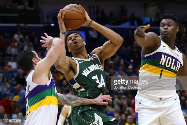 Giannis Antetokounmpo of the Milwaukee Bucks shoots against Zion Williamson of the New Orleans Pelicans and JJ Redick during the first half at the...