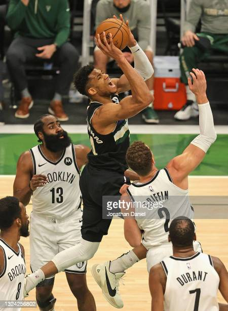 Giannis Antetokounmpo of the Milwaukee Bucks shoots between James Harden and Blake Griffin of the Brooklyn Nets at Fiserv Forum on June 17, 2021 in...