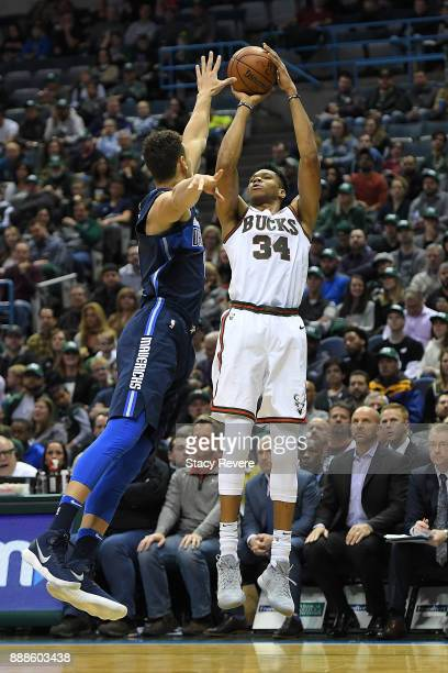 Giannis Antetokounmpo of the Milwaukee Bucks shoots over Dwight Powell of the Dallas Mavericks during the first half of a game at the Bradley Center...