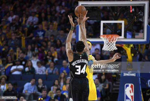 Giannis Antetokounmpo of the Milwaukee Bucks shoots over JaVale McGee of the Golden State Warriors during an NBA basketball game at ORACLE Arena on...