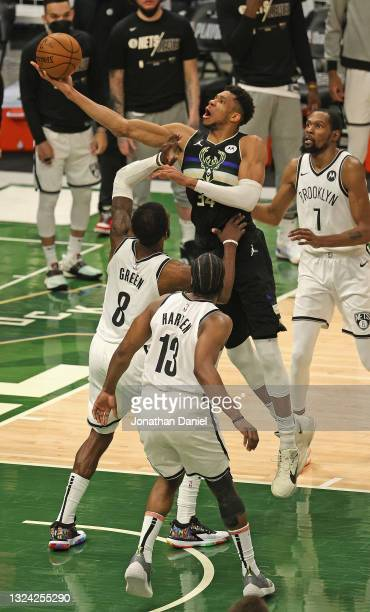 Giannis Antetokounmpo of the Milwaukee Bucks shoots over Jeff Green and James Harden of the Brooklyn Nets at Fiserv Forum on June 17, 2021 in...