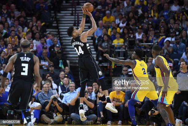 Giannis Antetokounmpo of the Milwaukee Bucks shoots over Jordan Bell of the Golden State Warriors during an NBA basketball game at ORACLE Arena on...