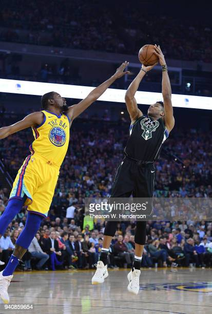 Giannis Antetokounmpo of the Milwaukee Bucks shoots over Kevin Durant of the Golden State Warriors during an NBA basketball game at ORACLE Arena on...