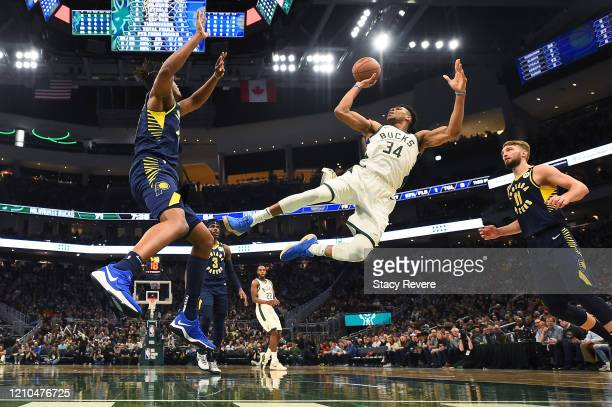 Giannis Antetokounmpo of the Milwaukee Bucks shoots over Myles Turner of the Indiana Pacers during a game at Fiserv Forum on March 04, 2020 in...