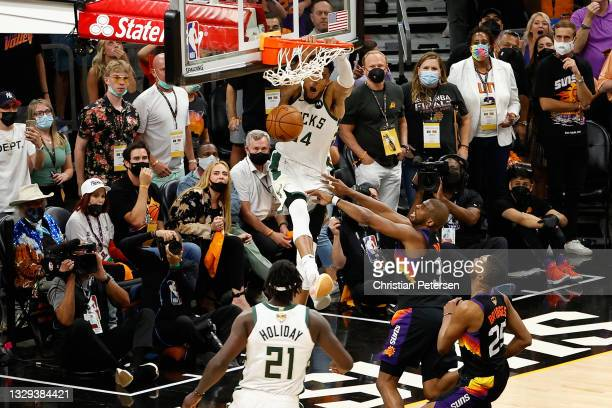 Giannis Antetokounmpo of the Milwaukee Bucks slam dunks the ball over Chris Paul of the Phoenix Suns late in the second half of game five of the NBA...