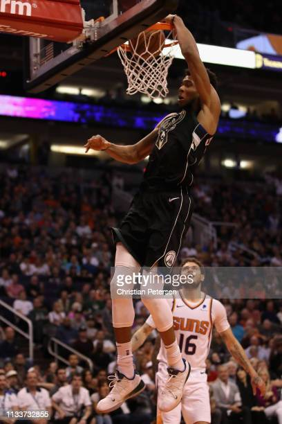 Giannis Antetokounmpo of the Milwaukee Bucks slam dunks the ball past Tyler Johnson of the Phoenix Suns during the second half of the NBA game at...