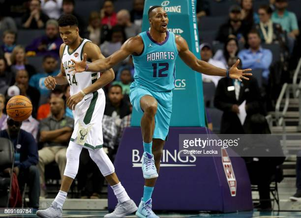 Giannis Antetokounmpo of the Milwaukee Bucks watches on as Dwight Howard of the Charlotte Hornets reacts after a call during their game at Spectrum...