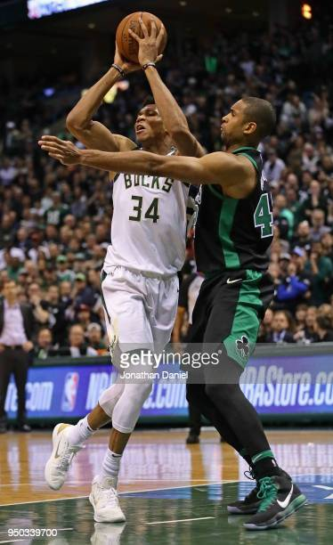 Giannis Antetokounmpo of the Milwaukee Buckspasses under pressure from Al Horford of the Boston Celtics during Game Four of Round One of the 2018 NBA...