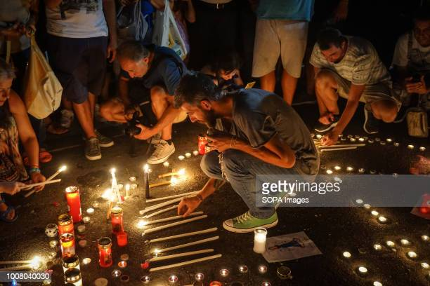 Giannis Gkakaloudis former player of Panathinaikos Basketball team places a candle during a silent protest People gathered outside the Hellenic...