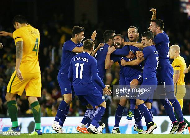 Giannis Maniatis of Greece is congratulated by his teammates after kicking a goal from half way as Tim Cahill and Aaron Mooy of Australia look...