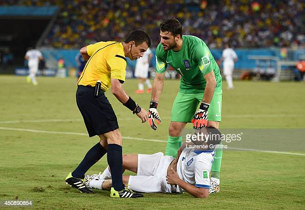 Giannis Maniatis of Greece lies on the field after a challenge as referee Joel Aguilar and teammate goalkeeper Orestis Karnezis look on during the...