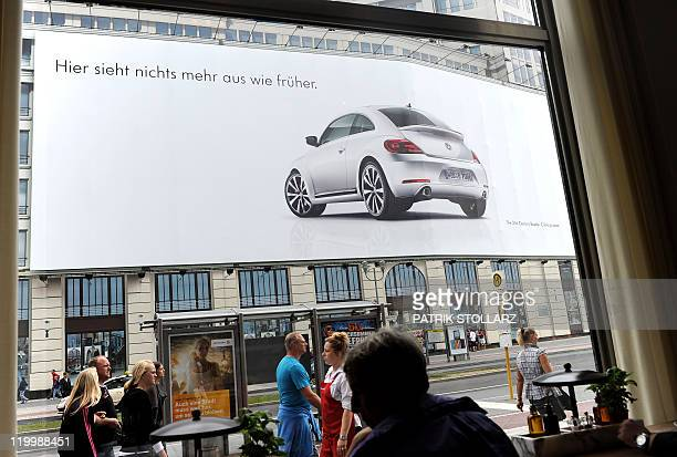 A giant advertisement promotes the beetle car by German car maker Volkswagen on July 28 2011 in Berlin AFP PHOTO / PATRIK STOLLARZ